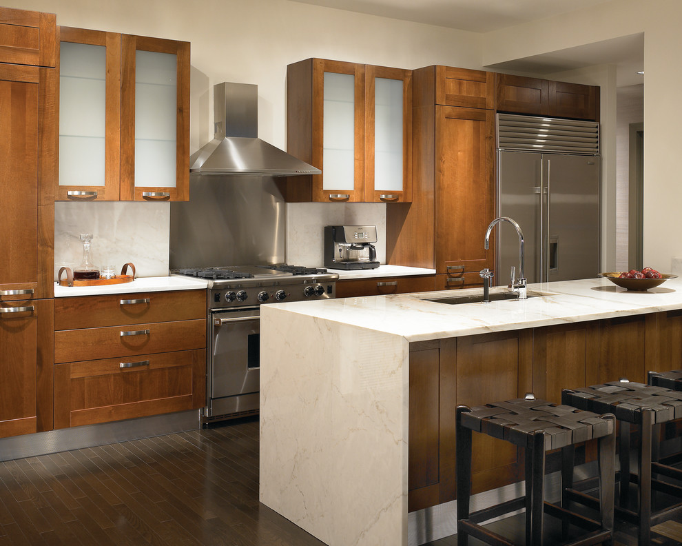 Example of a trendy galley kitchen design in Chicago with stainless steel appliances, an undermount sink, shaker cabinets, medium tone wood cabinets, stone slab backsplash, granite countertops and white backsplash