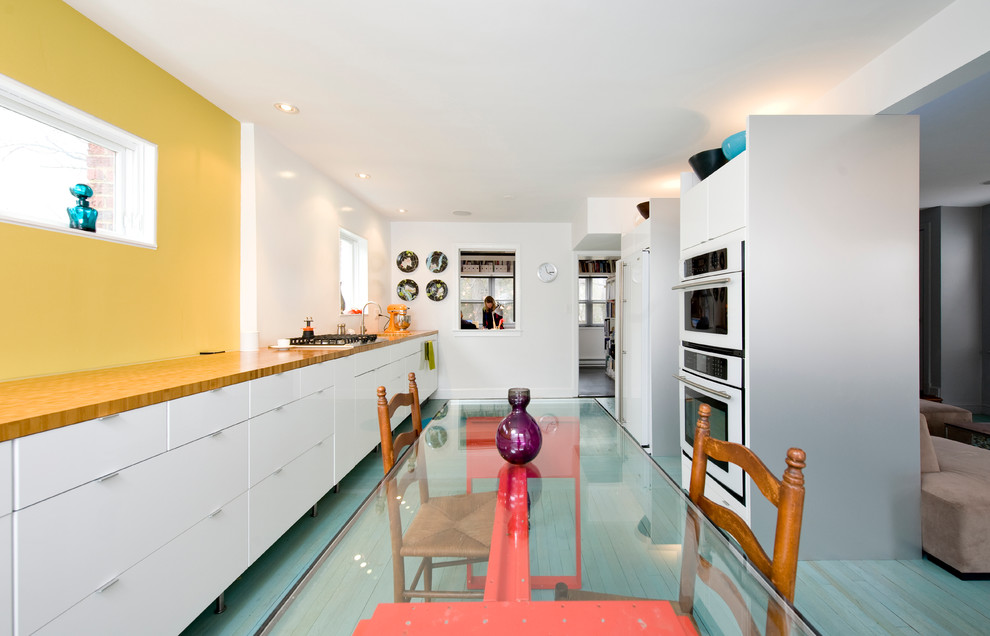 Trendy galley turquoise floor eat-in kitchen photo in DC Metro with flat-panel cabinets, white cabinets, wood countertops and white appliances