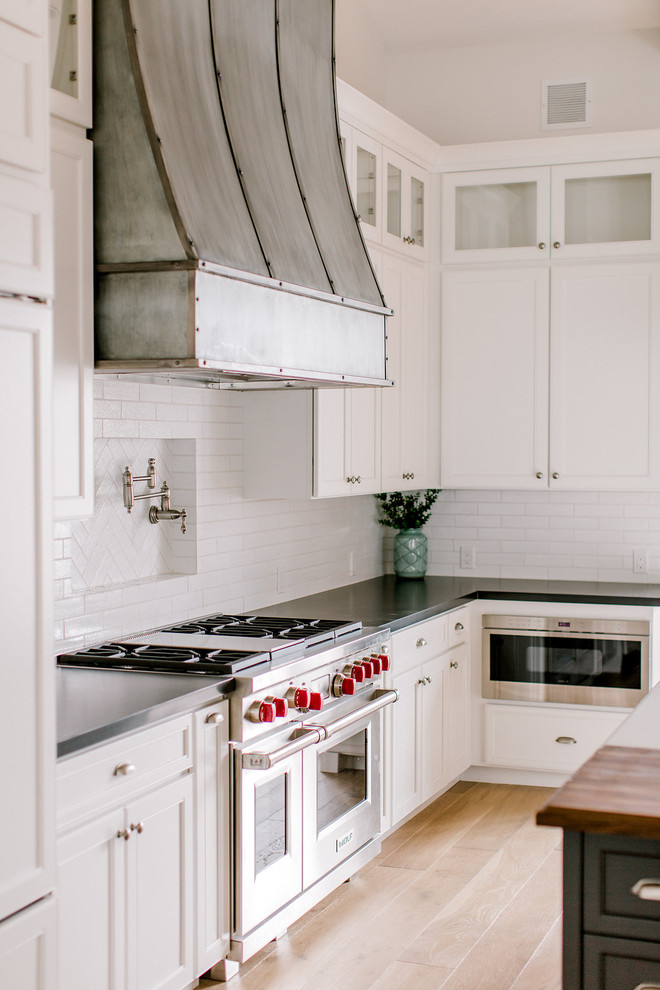 Inspiration for a cottage l-shaped light wood floor open concept kitchen remodel in Phoenix with a farmhouse sink, shaker cabinets, white cabinets, quartz countertops, white backsplash, brick backsplash, stainless steel appliances and an island