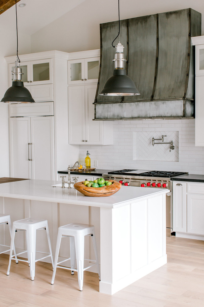Example of a cottage light wood floor and beige floor kitchen design in Phoenix with an undermount sink, shaker cabinets, white cabinets, white backsplash, paneled appliances, an island and white countertops