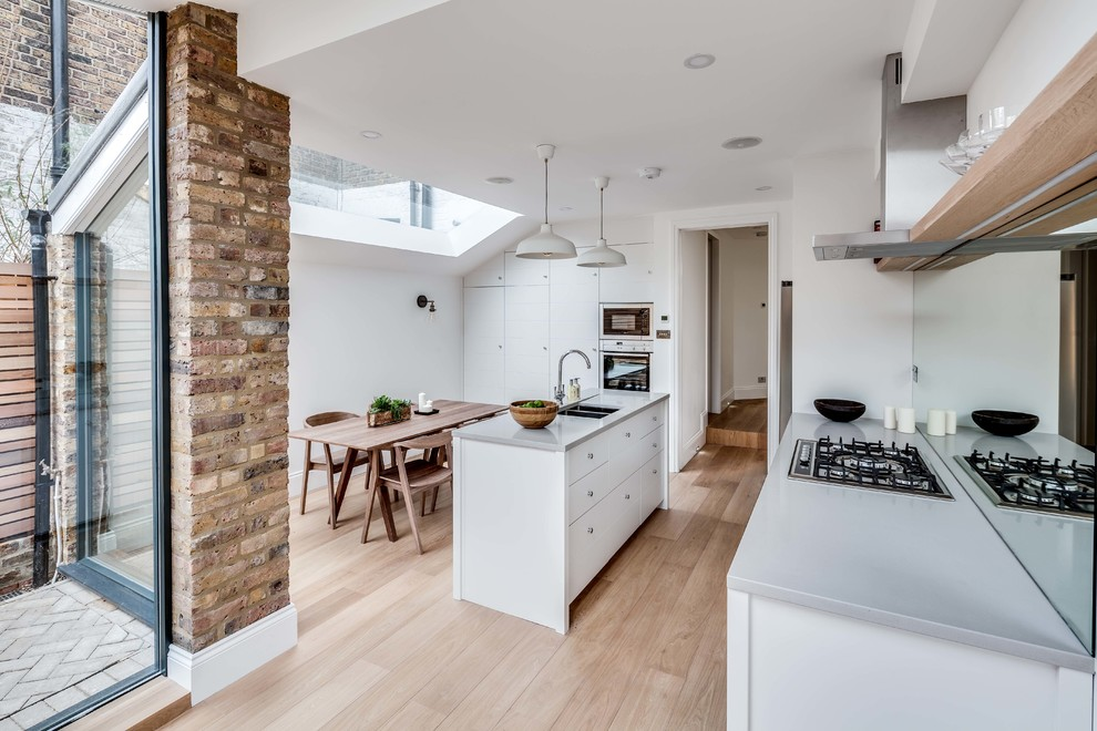 Danish galley light wood floor eat-in kitchen photo in London with an undermount sink, flat-panel cabinets, white cabinets, mirror backsplash and an island