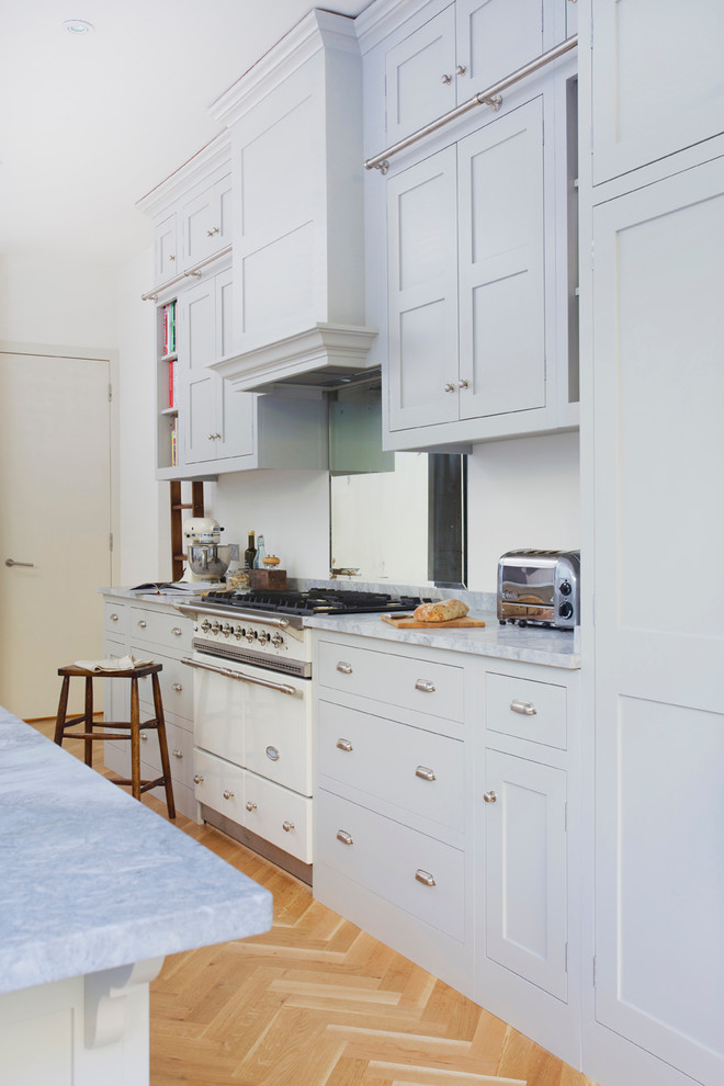 Kitchen - traditional kitchen idea in Surrey with shaker cabinets and an island