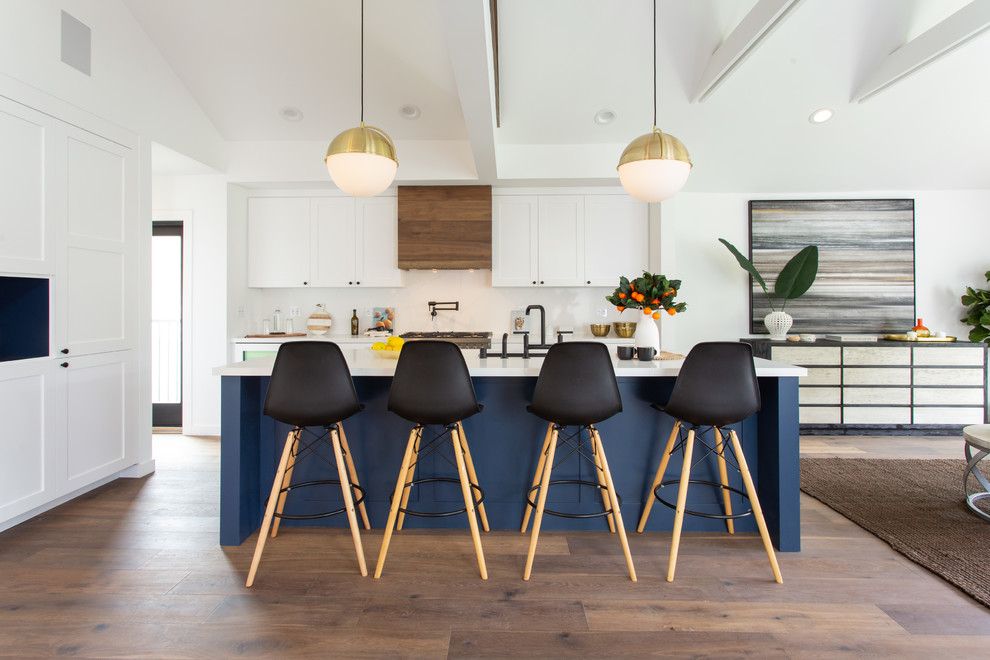 Transitional dark wood floor and brown floor open concept kitchen photo in Los Angeles with an undermount sink, shaker cabinets, white cabinets, white backsplash, an island and white countertops