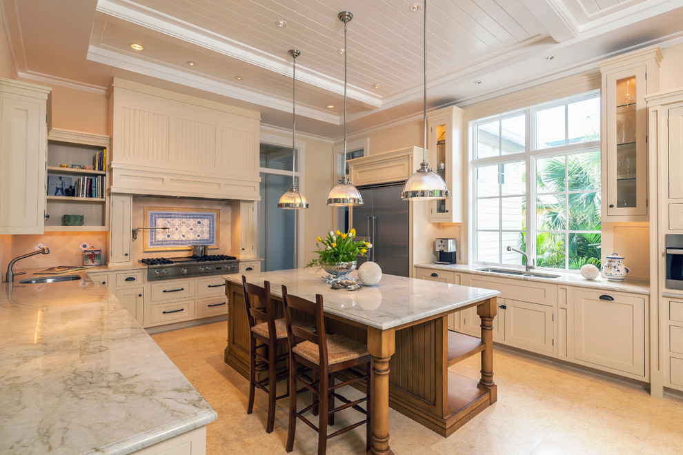 Kitchen - traditional u-shaped kitchen idea in Miami with beige cabinets and stainless steel appliances
