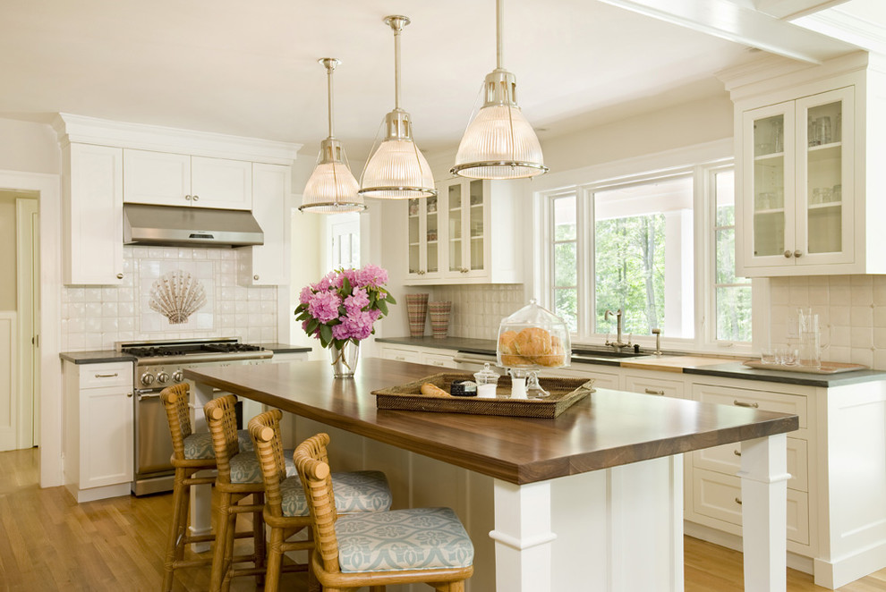 Example of a large classic galley medium tone wood floor eat-in kitchen design in Boston with glass-front cabinets, stainless steel appliances, white cabinets, an undermount sink, white backsplash, ceramic backsplash, an island and wood countertops