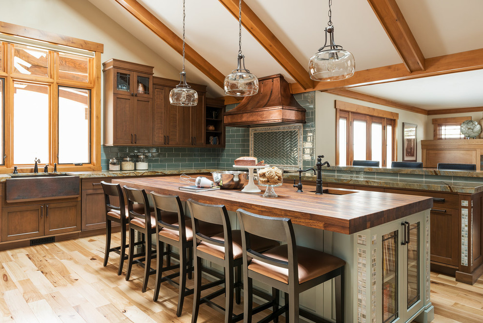 Open concept kitchen - craftsman l-shaped light wood floor and beige floor open concept kitchen idea in Salt Lake City with a farmhouse sink, shaker cabinets, dark wood cabinets, wood countertops, green backsplash, subway tile backsplash and an island