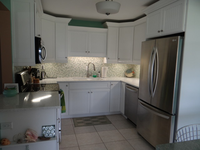 Example of a small coastal u-shaped ceramic floor open concept kitchen design in Tampa with an undermount sink, shaker cabinets, white cabinets, quartz countertops, green backsplash, glass tile backsplash, stainless steel appliances and an island
