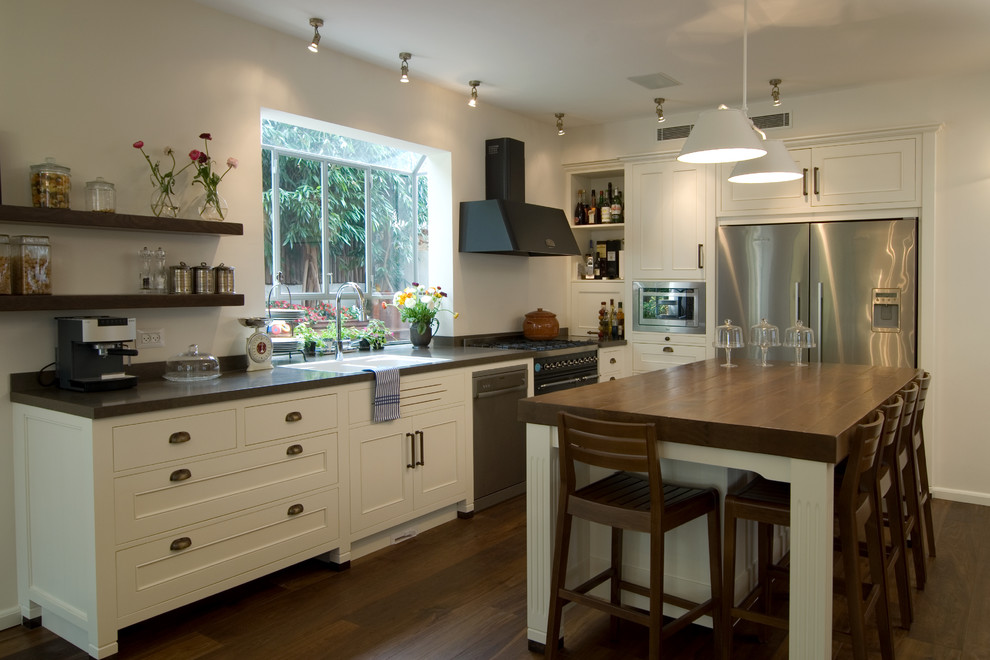 Inspiration for a contemporary l-shaped kitchen remodel in Tel Aviv with stainless steel appliances, a drop-in sink and white cabinets