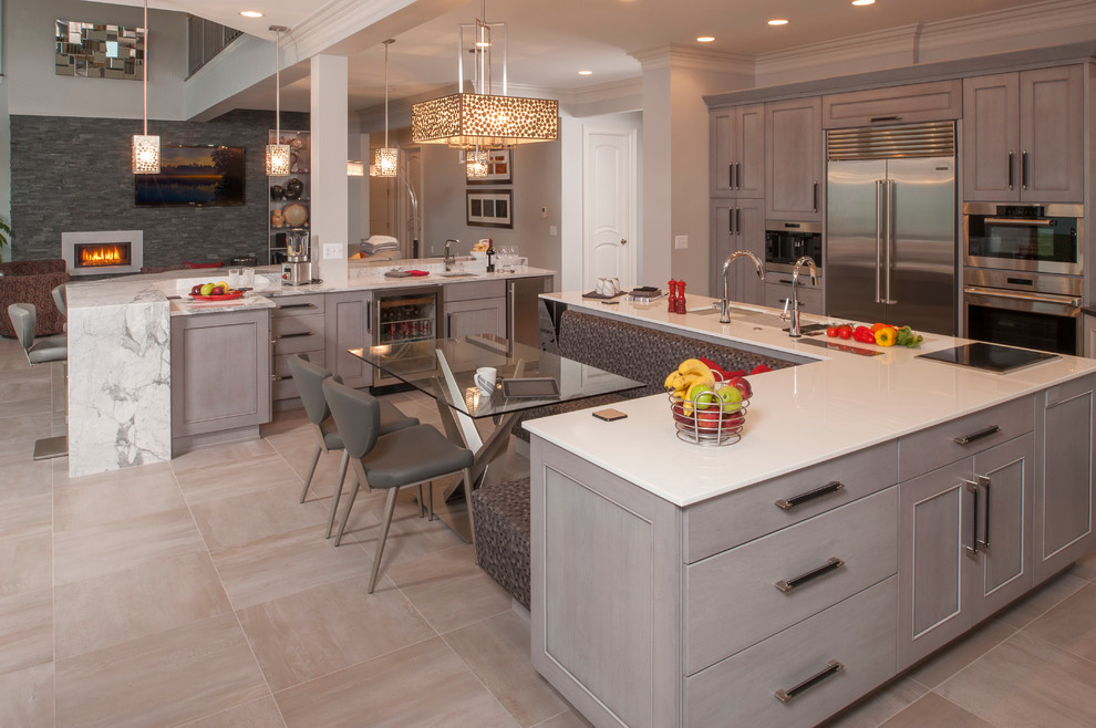 Inspiration for a large transitional l-shaped ceramic tile open concept kitchen remodel in Detroit with an undermount sink, recessed-panel cabinets, white cabinets, quartz countertops, white backsplash, subway tile backsplash, stainless steel appliances and two islands