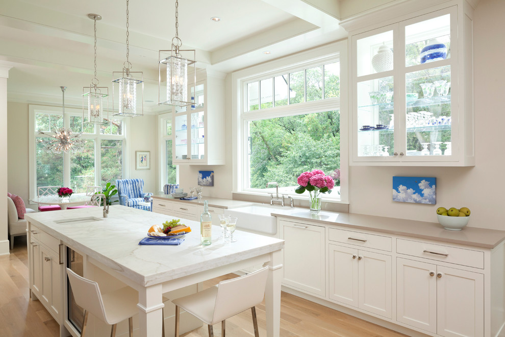 Mid-sized elegant single-wall light wood floor open concept kitchen photo in Minneapolis with a farmhouse sink, shaker cabinets, white cabinets, an island, marble countertops, white backsplash, stone slab backsplash and stainless steel appliances
