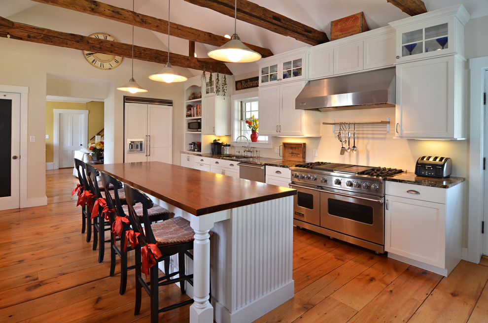 Example of a country l-shaped medium tone wood floor kitchen design in Boston with shaker cabinets, white cabinets, an island, an undermount sink, granite countertops, white backsplash and stainless steel appliances
