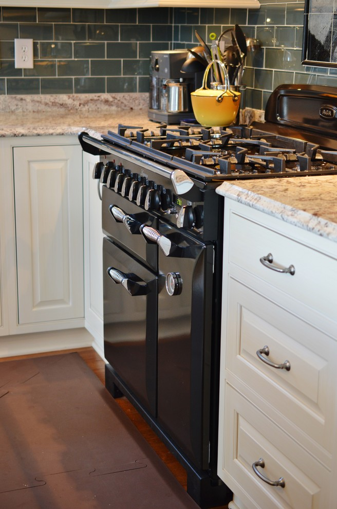 Mid-sized elegant l-shaped dark wood floor eat-in kitchen photo in DC Metro with a farmhouse sink, raised-panel cabinets, white cabinets, granite countertops, blue backsplash, glass tile backsplash, paneled appliances and an island
