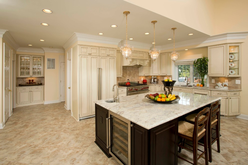 Inspiration for a mid-sized timeless l-shaped travertine floor and beige floor open concept kitchen remodel in DC Metro with a double-bowl sink, raised-panel cabinets, beige cabinets, granite countertops, beige backsplash, stone slab backsplash, stainless steel appliances and an island