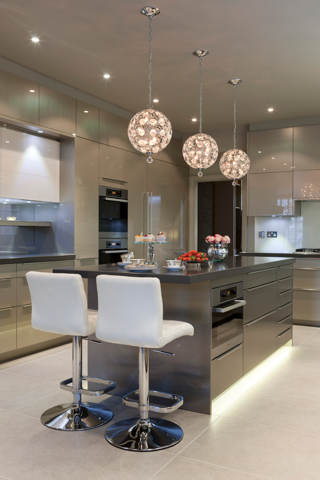 Kitchen - large contemporary u-shaped ceramic tile kitchen idea in London with flat-panel cabinets, stainless steel appliances, an island, gray cabinets and glass sheet backsplash
