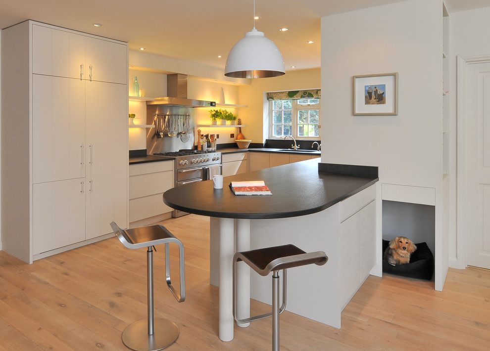 Example of a trendy u-shaped kitchen design in Hampshire with flat-panel cabinets and white cabinets