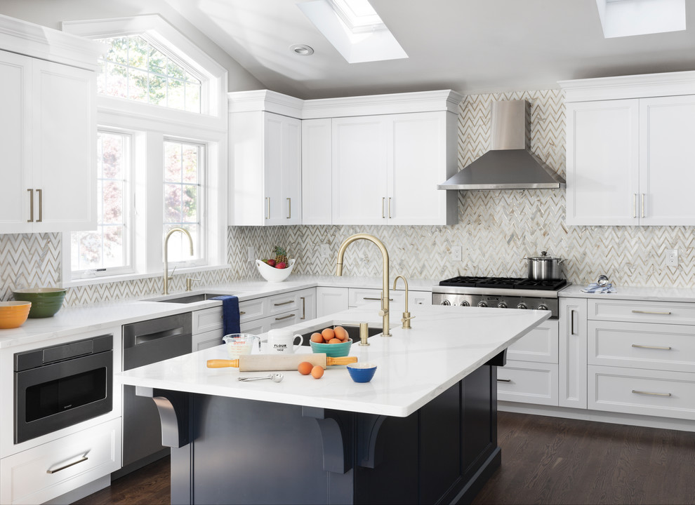 Mid-sized trendy u-shaped medium tone wood floor and brown floor enclosed kitchen photo in New York with a drop-in sink, shaker cabinets, white cabinets, quartzite countertops, gray backsplash, marble backsplash, stainless steel appliances, an island and white countertops