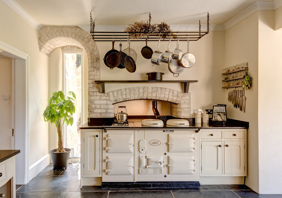 Eat-in kitchen - huge farmhouse slate floor eat-in kitchen idea in Devon with beaded inset cabinets, beige cabinets, granite countertops and white appliances