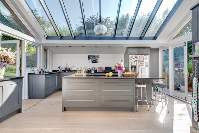 Design ideas for a large contemporary l-shaped kitchen/diner in Devon with a submerged sink, shaker cabinets, grey cabinets, granite worktops, stainless steel appliances, light hardwood flooring and an island.
