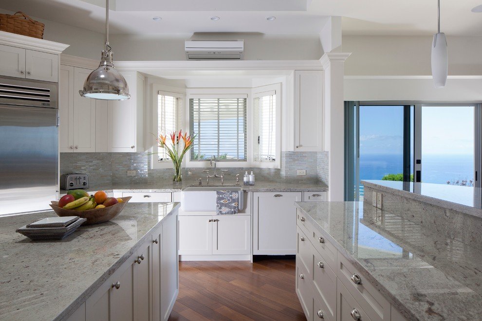 Island style kitchen photo in Hawaii with a farmhouse sink, shaker cabinets, white cabinets, stainless steel appliances and granite countertops