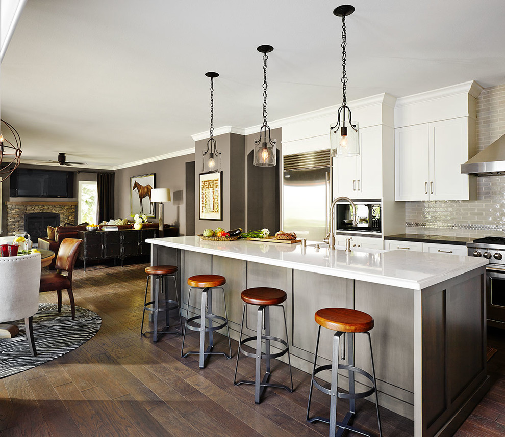 Eat-in kitchen - large transitional l-shaped dark wood floor eat-in kitchen idea in San Francisco with a farmhouse sink, shaker cabinets, white cabinets, beige backsplash, stainless steel appliances, an island, quartz countertops and subway tile backsplash