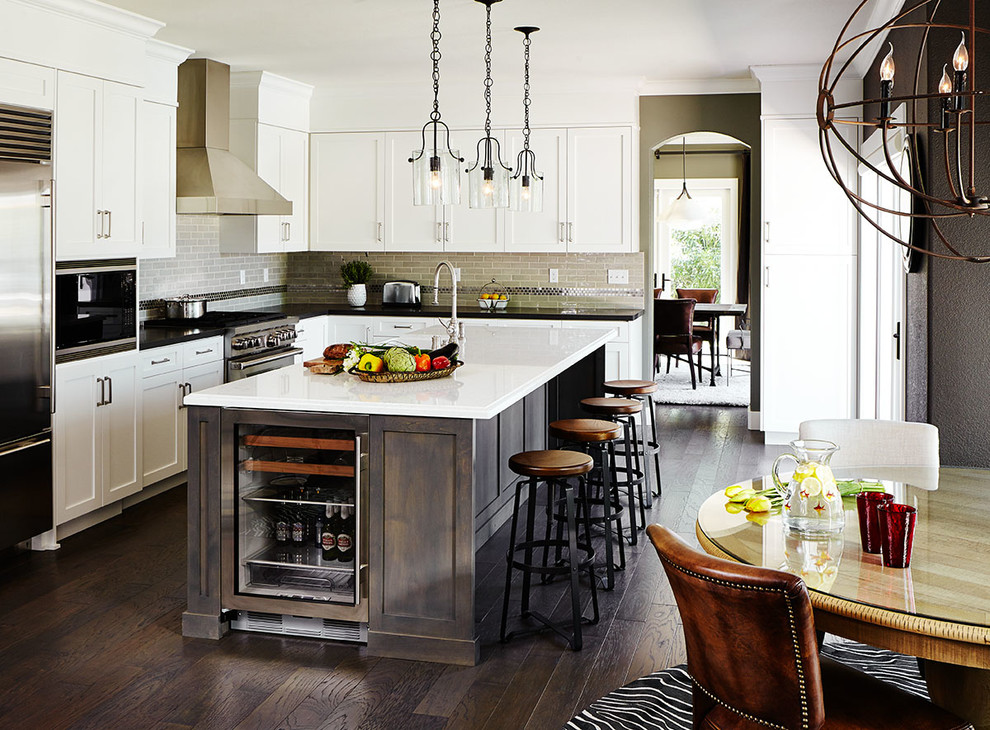 Example of a large transitional l-shaped dark wood floor open concept kitchen design in San Francisco with a farmhouse sink, shaker cabinets, quartz countertops, beige backsplash, subway tile backsplash, stainless steel appliances and an island