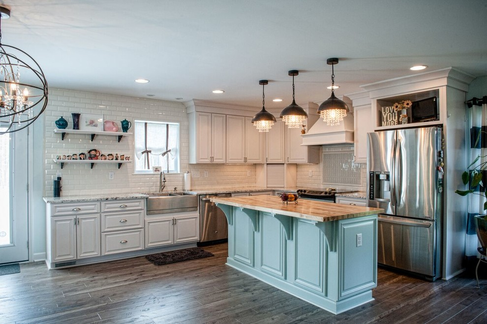 Example of a large transitional l-shaped dark wood floor eat-in kitchen design in Charlotte with a farmhouse sink, raised-panel cabinets, white cabinets, granite countertops, white backsplash, stainless steel appliances, an island and subway tile backsplash