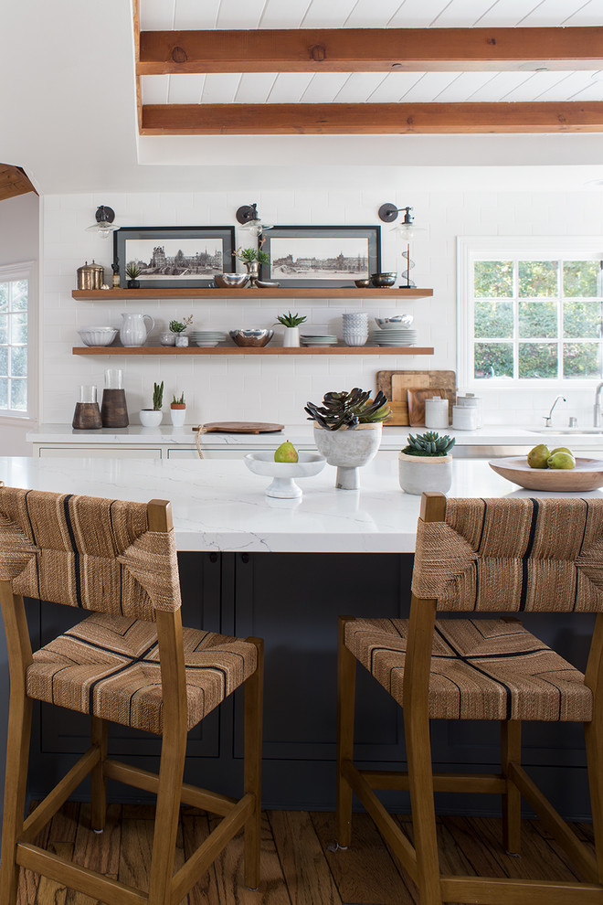 Large transitional l-shaped light wood floor and brown floor open concept kitchen photo in Los Angeles with an undermount sink, shaker cabinets, quartz countertops, stainless steel appliances, an island, white cabinets, white backsplash, white countertops and subway tile backsplash