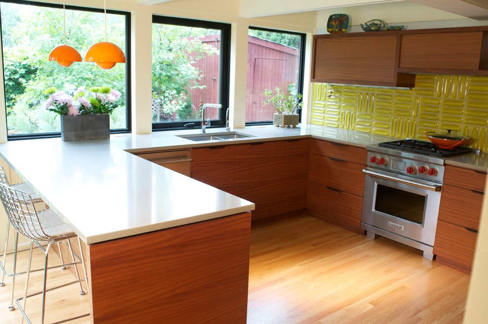 Inspiration for a mid-sized modern u-shaped light wood floor kitchen remodel in Denver with a double-bowl sink, flat-panel cabinets, medium tone wood cabinets, quartz countertops, yellow backsplash, stainless steel appliances and a peninsula