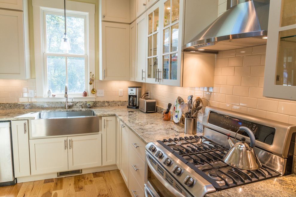 Inspiration for a farmhouse kitchen remodel in Other with a farmhouse sink, recessed-panel cabinets, white cabinets, white backsplash, subway tile backsplash and stainless steel appliances