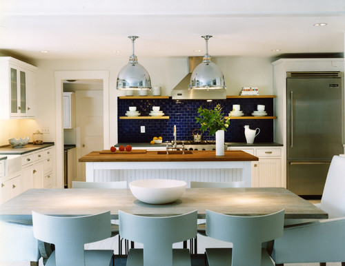 White and Navy Blue kitchen design with an indigo blue subway-tile backsplash, white cabinets, gray and wood countertops and large oversized industrial pendant lights.