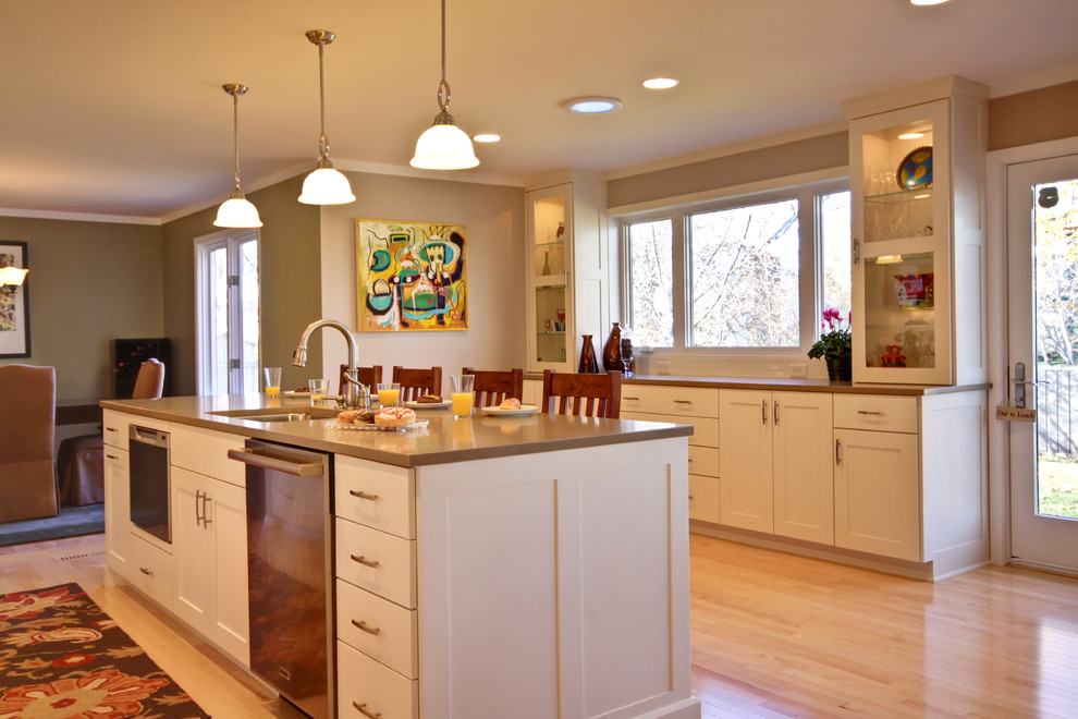 Elegant kitchen photo in Minneapolis with glass-front cabinets and stainless steel appliances