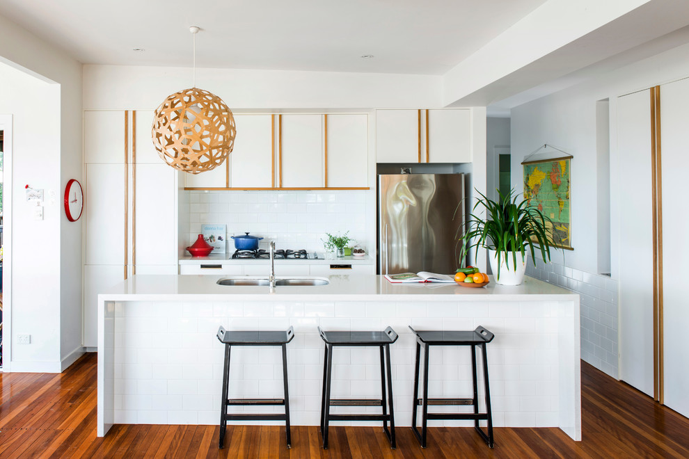 Kitchen - contemporary kitchen idea in Gold Coast - Tweed with flat-panel cabinets, white cabinets, white backsplash, stainless steel appliances and an island