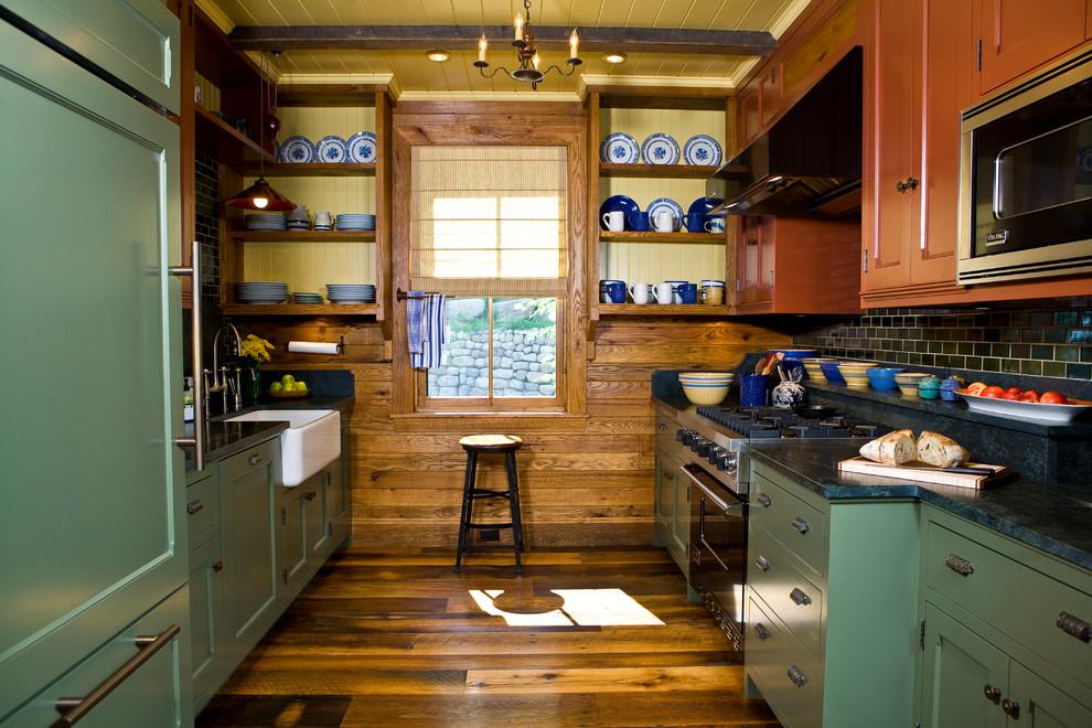 Kitchen - rustic galley medium tone wood floor kitchen idea in Burlington with a farmhouse sink, shaker cabinets, black backsplash, subway tile backsplash, black appliances and no island