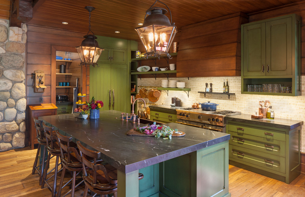 Inspiration for a huge rustic medium tone wood floor kitchen remodel in Grand Rapids with a farmhouse sink, shaker cabinets, green cabinets, beige backsplash, stainless steel appliances, an island and black countertops