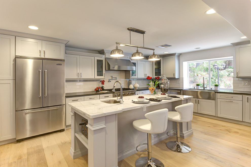 Inspiration for a transitional l-shaped light wood floor kitchen remodel in Los Angeles with a farmhouse sink, shaker cabinets, gray cabinets, white backsplash, subway tile backsplash, stainless steel appliances and an island