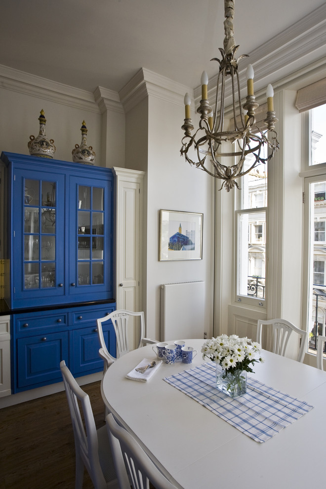 Elegant eat-in kitchen photo in London with blue cabinets