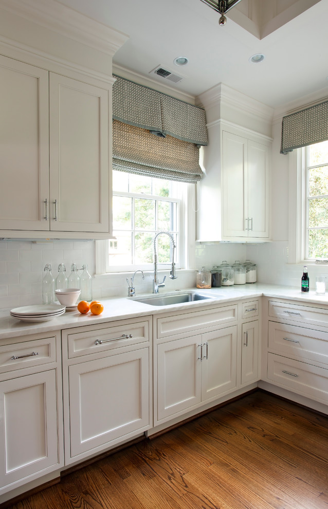 Example of a classic kitchen design in Charlotte with shaker cabinets, white cabinets, white backsplash and subway tile backsplash