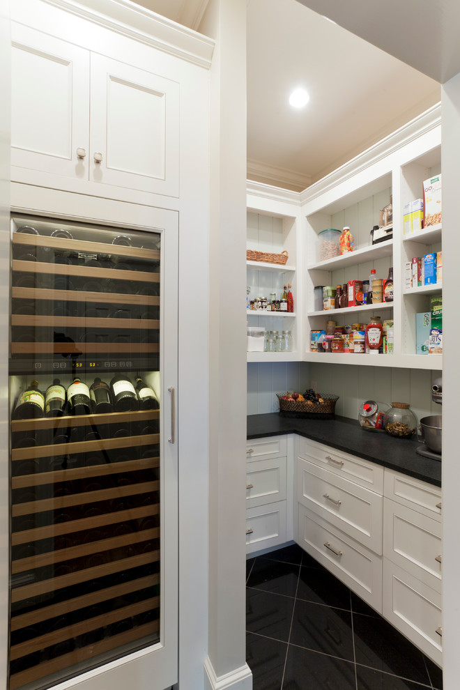 Example of a classic kitchen pantry design in Charlotte with recessed-panel cabinets, white cabinets and white backsplash