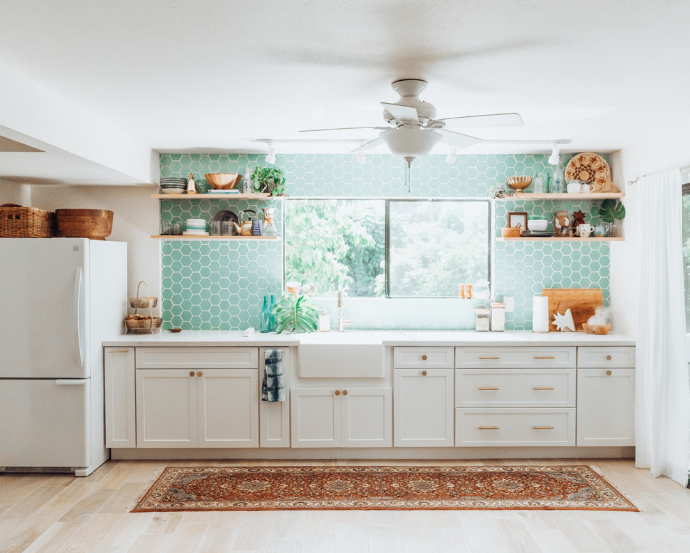 Mid-sized transitional light wood floor kitchen photo in Hawaii with blue backsplash, ceramic backsplash, a farmhouse sink, shaker cabinets, white cabinets, white appliances and no island