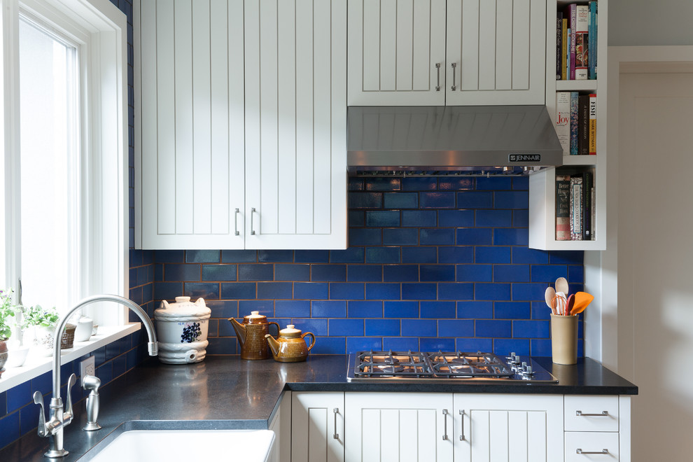 Eat-in kitchen - contemporary u-shaped eat-in kitchen idea in Portland with stainless steel appliances, a farmhouse sink, white cabinets, granite countertops, blue backsplash, subway tile backsplash and recessed-panel cabinets