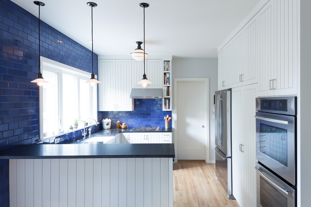 Example of a trendy u-shaped eat-in kitchen design in Portland with stainless steel appliances, ceramic backsplash, a farmhouse sink, granite countertops, blue backsplash, white cabinets and beaded inset cabinets