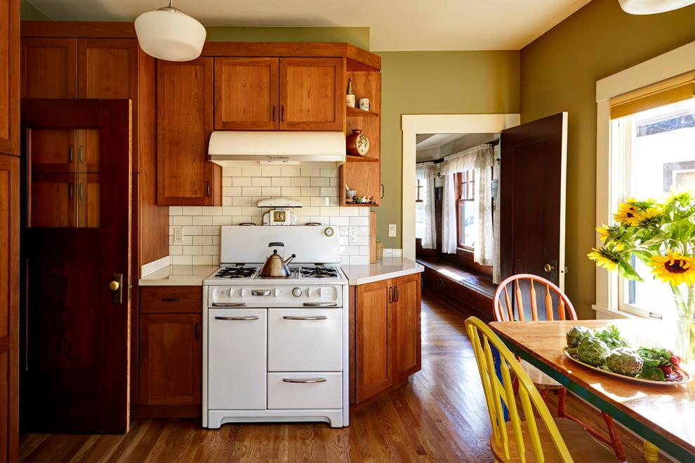 Mid-sized arts and crafts medium tone wood floor enclosed kitchen photo in San Francisco with an undermount sink, shaker cabinets, medium tone wood cabinets, quartz countertops, white backsplash, ceramic backsplash and white appliances