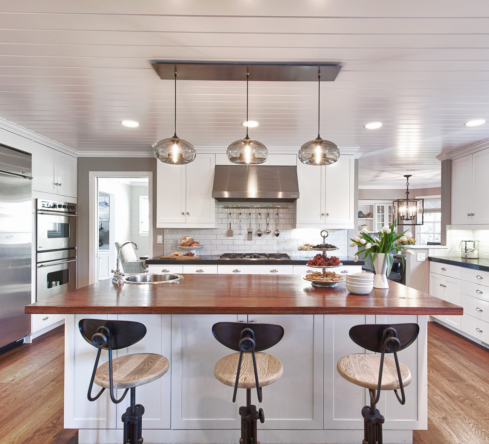 Example of a large trendy u-shaped medium tone wood floor and brown floor eat-in kitchen design in San Francisco with wood countertops, shaker cabinets, white cabinets, white backsplash, stainless steel appliances, an island and subway tile backsplash