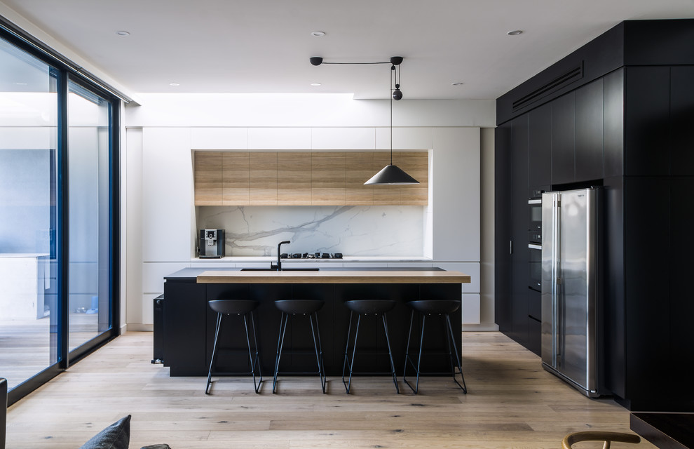 Inspiration for a mid-sized modern u-shaped light wood floor eat-in kitchen remodel in Melbourne with flat-panel cabinets, stone slab backsplash, an island, a single-bowl sink and stainless steel appliances