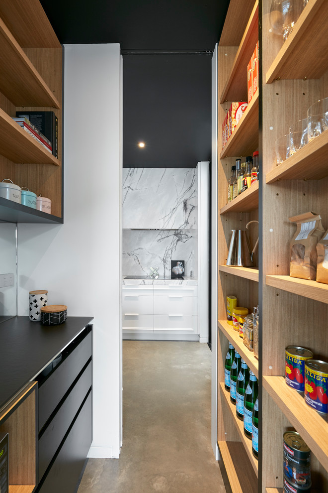 Example of a mid-sized trendy l-shaped concrete floor and gray floor kitchen pantry design in Melbourne with an undermount sink, beaded inset cabinets, black cabinets, quartz countertops, gray backsplash, marble backsplash, colored appliances, an island and black countertops