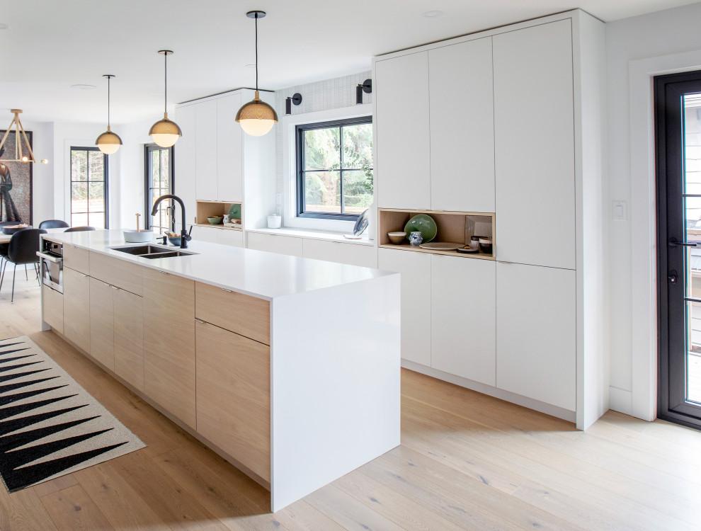 Diseño de cocina contemporánea con fregadero bajoencimera, armarios con paneles lisos, puertas de armario blancas, suelo de madera clara, una isla, suelo beige y encimeras blancas