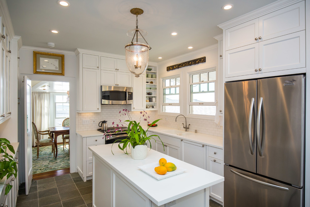 Example of a classic u-shaped kitchen pantry design in Hawaii with a double-bowl sink, shaker cabinets, white cabinets, white backsplash, stainless steel appliances, an island and subway tile backsplash