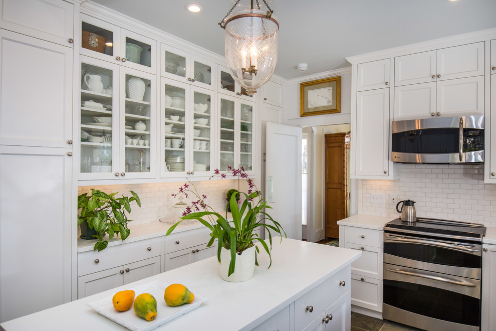 Inspiration for a large timeless u-shaped kitchen pantry remodel in Hawaii with a double-bowl sink, shaker cabinets, white cabinets, white backsplash, stainless steel appliances, an island and subway tile backsplash