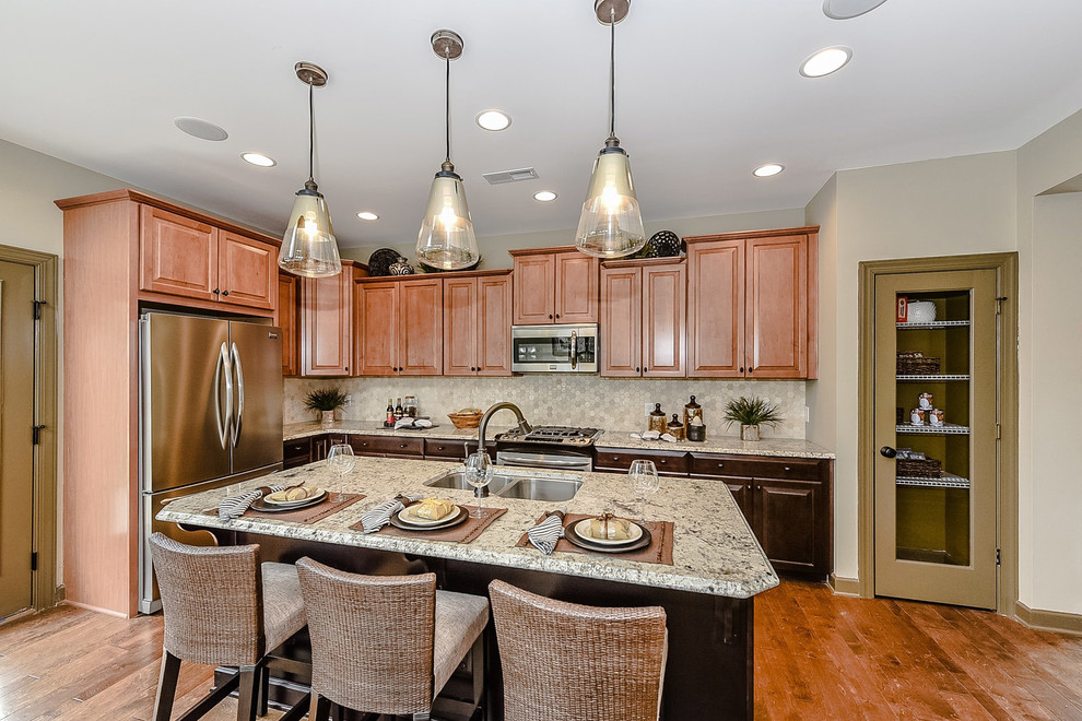 Inspiration for a small timeless l-shaped light wood floor open concept kitchen remodel in Charlotte with a double-bowl sink, raised-panel cabinets, granite countertops, multicolored backsplash, mosaic tile backsplash, stainless steel appliances, an island and medium tone wood cabinets
