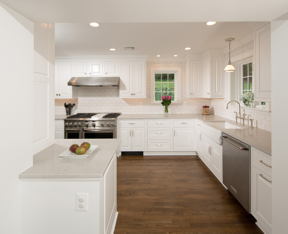 Inspiration for a mid-sized timeless u-shaped medium tone wood floor and brown floor enclosed kitchen remodel in DC Metro with a farmhouse sink, raised-panel cabinets, white cabinets, quartz countertops, gray backsplash, subway tile backsplash, stainless steel appliances and a peninsula